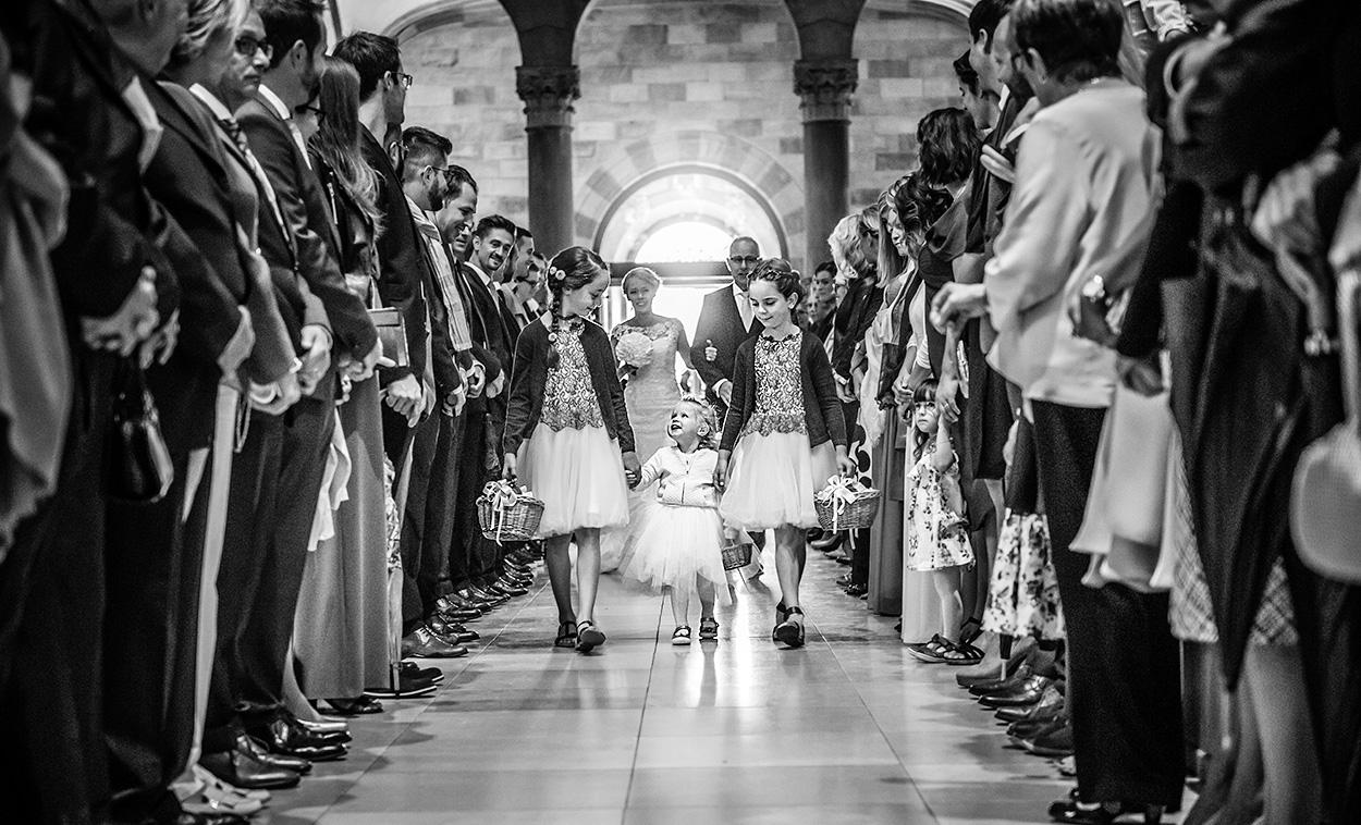 Hochzeitsfoto zeigt Einzug des Brautpaares in die Kirche der Basilika Echternach mit Kindern im Vordergrund