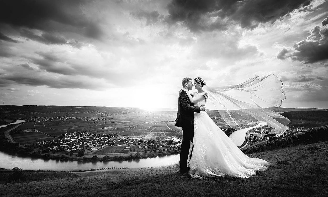 Brautpaar hoch über der Mosel als Panorama Hochzeitsfoto bei Trier mit dramatischen Wolken in schwarzweiß
