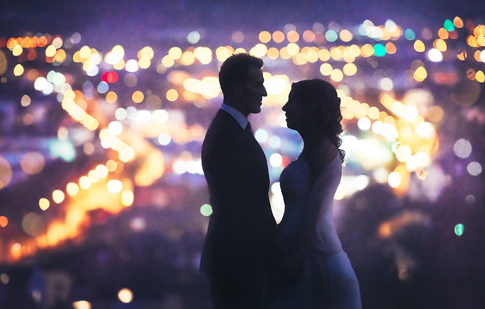 Hochzeitsfoto vor dem Robert Schuman Haus in Trier mit den Lichtern der Stadt im Hintergrund.