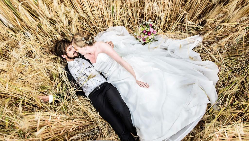 Fotografie einer Hochzeit in Trier - Brautpaar liegt im Kornfeld
